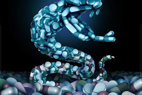 Opioids and opioid health risk and medical crisis with a prescription painkiller addiction epidemic concept as a group pills shaped as a snake with 3D illustration elements.